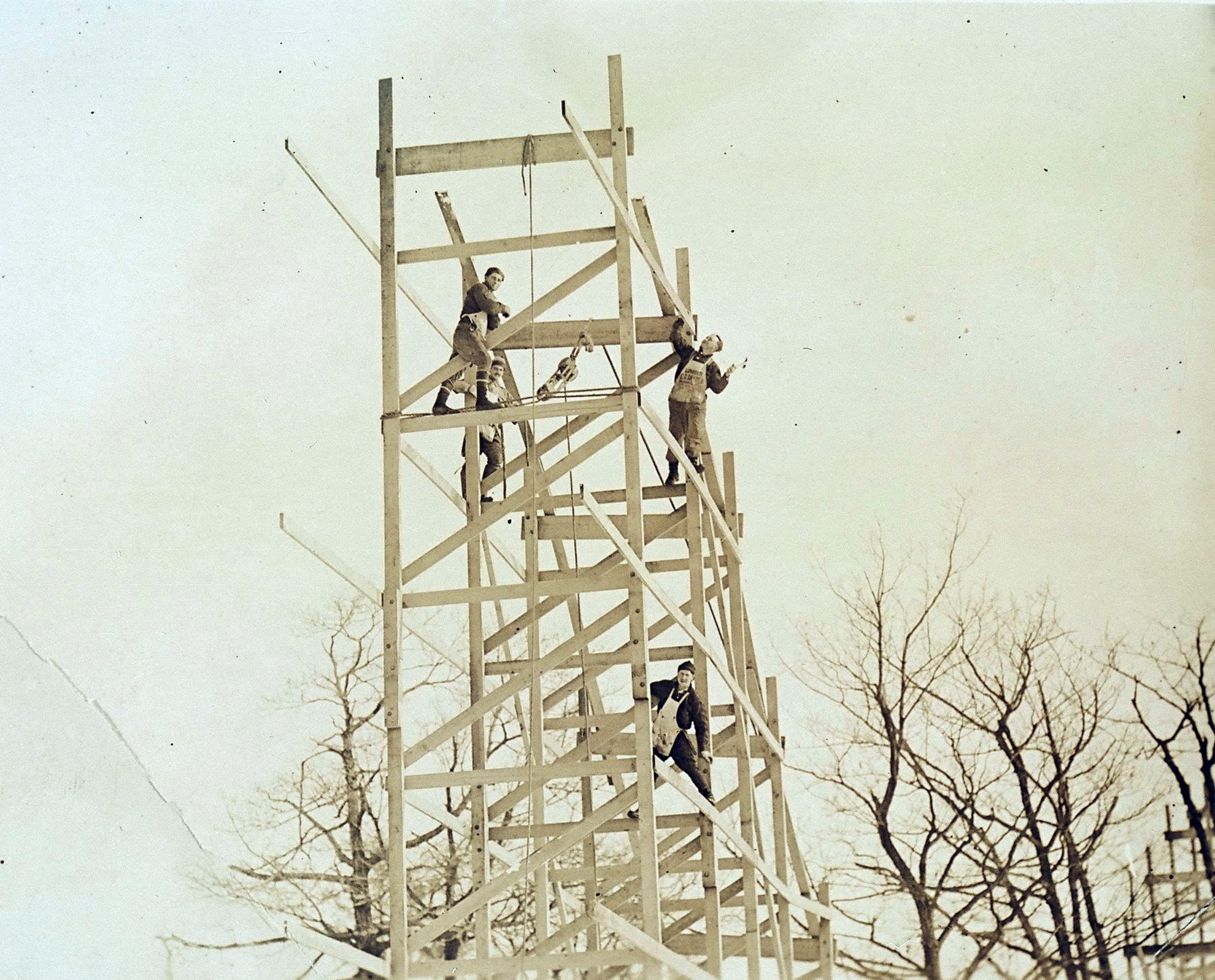 1920s workers assembling a wooden roller coaster hill