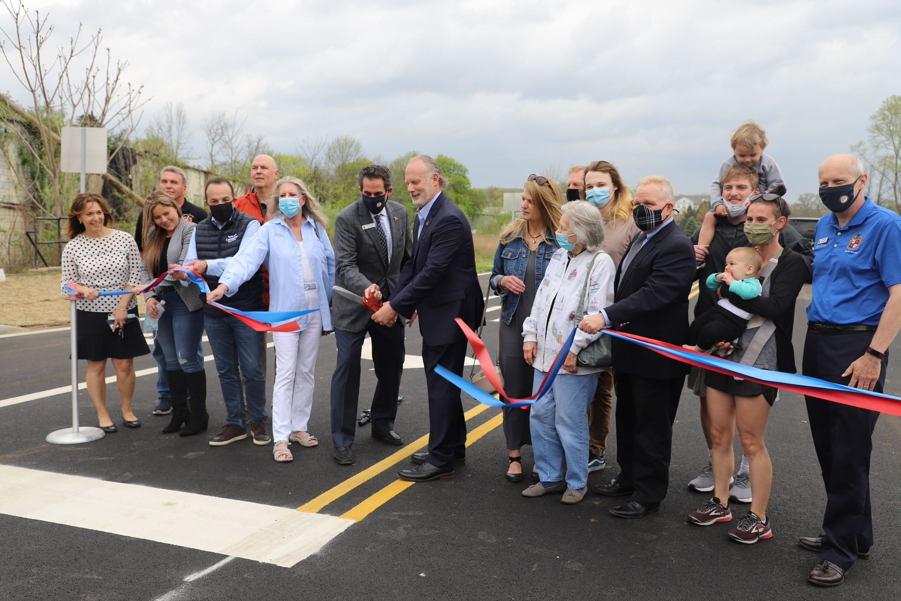 Mayor Chegwidden cut the ribbon to open Chegwidden Way while surrounded by the Morris County Board of County Commissioners, his family and Wharton employees.