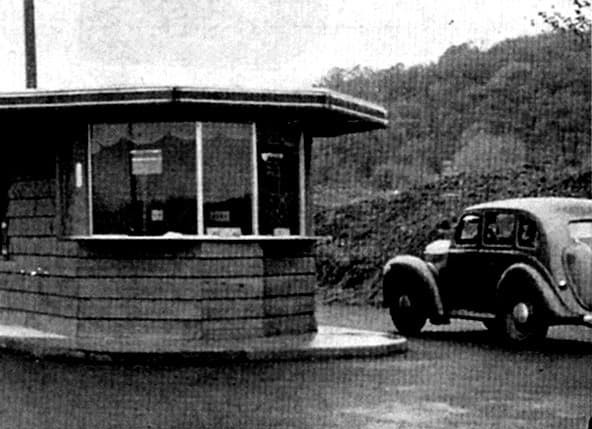A vintage car approaching the toll booth and office.