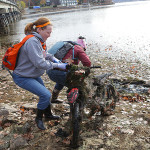 During the November lake-wide cleanup, volunteers Michele Meyer, left, and Yvonne Syto, right, struggle to remove a dirt bike found buried in the muck near the River Styx Bridge in Hopatcong.