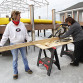 Lisa Palanchi, right, cuts a two by four using a miter saw while standing on the ice near her dock in Mount Arlington. Holding the board is Patti Cinelli, left.