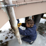 Lisa Palanchi takes advantage of the 60-inch drawdown and the frozen lake to perform repairs under her dock in Mount Arlington.