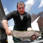 Chase Mancini, third generation owner at Musky Trout Hatchery, shows off the largest trophy fish, a 26-inch rainbow trout, being stocked in Lake Hopatcong during the annual Knee Deep Club trout stocking event, Saturday, April 26.