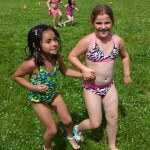 Ava Jimenez,7, and Destiny Dolton, 7, run to cross the finish line during the three-legged race.