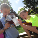 Students from Edith M. Decker School look at a sample of water from Lake Hopatcong while visiting a historic boathouse.