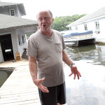 Joseph Bongiovanni, standing on his dock, uses his hands to explain the size of the head of the boa costrictor he saw in Lake Hopatcong.