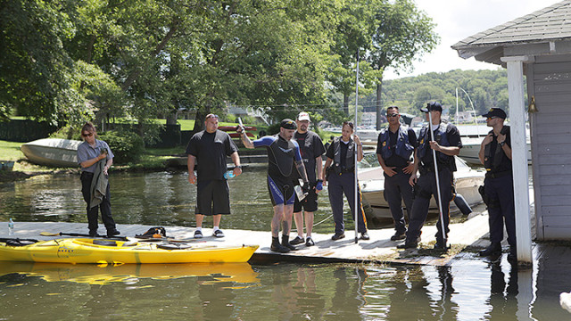 Gerald Andrejcak, a reptile specialist, center, with marine police and Hopatcong animal control, searching for a snake in the lake last Thursday.