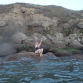 Bridgette Hobart Janeczko celebrates on the rocky shoreline of France after swimming the English Channel.