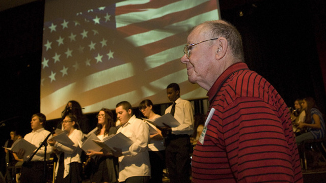 Army veteran Roy McQueen stands as the Army theme song is performed by Hopatcong High School chorus.