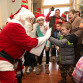 Dillon Consalazio gets a high five from Santa at the Toys For Tots kickoff party.