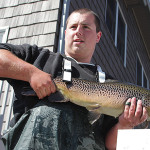 Chase Mancini from Musky Trout Hatchery shows off one of two trophy fish, a brown trout.